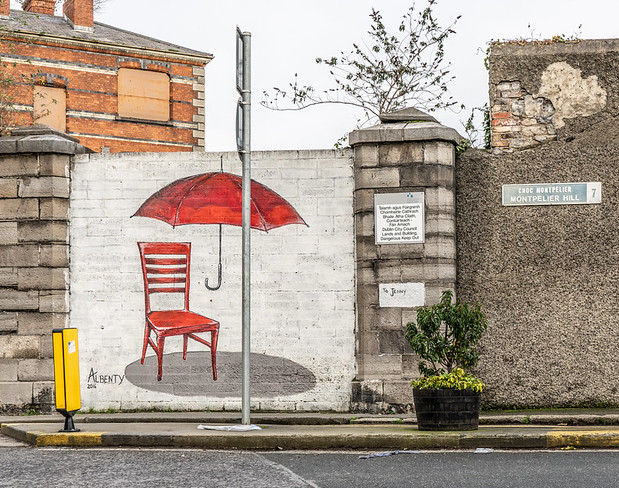 Picture of mural street art with empty red chair with floating red umbrella